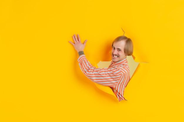 感情的で表情豊かな破れた黄色い紙の穴の壁で陽気な若い男のポーズ