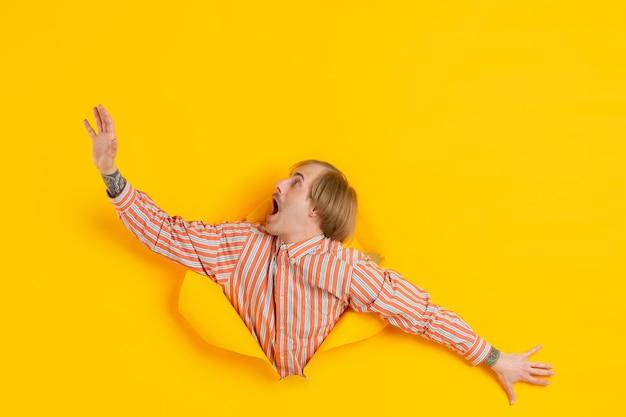 Жизнерадостный молодой человек позирует в рваной желтой стене с отверстиями для бумаги эмоционально и выразительно