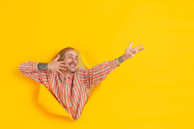 陽気な若い男は、感情的で表現力豊かな引き裂かれた黄色い紙の穴の壁でポーズをとる