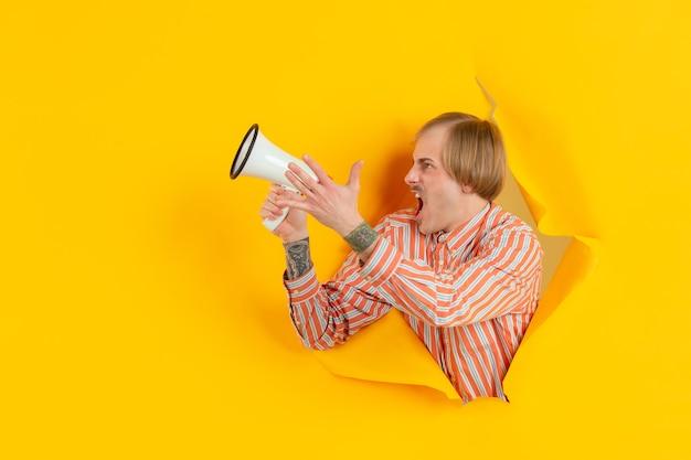 陽気な若い男は、感情的で表現力豊かな黄色の紙の穴の壁を引き裂かれたポーズ