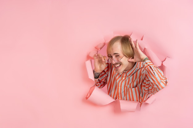 Cheerful young man poses in torn coral paper hole wall emotional and expressive