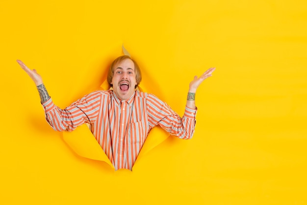 Cheerful young man poses in torn yellow paper hole wall emotional and expressive