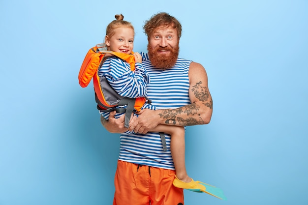 Cheerful young man poses with little ginger girl who wears orange lifevest, rubber fins, happy to spend summer holiday with father, enjoys swimming