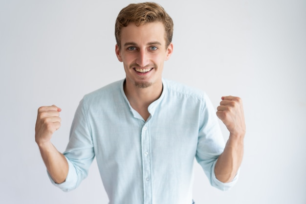 陽気な若い男の拳をポンピングとカメラ目線