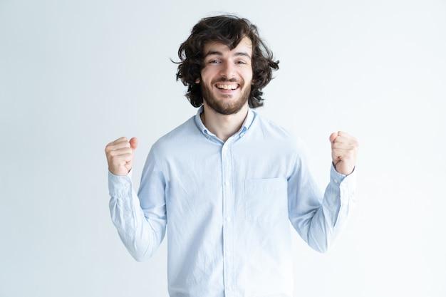 Cheerful young man pumping fists and looking at camera