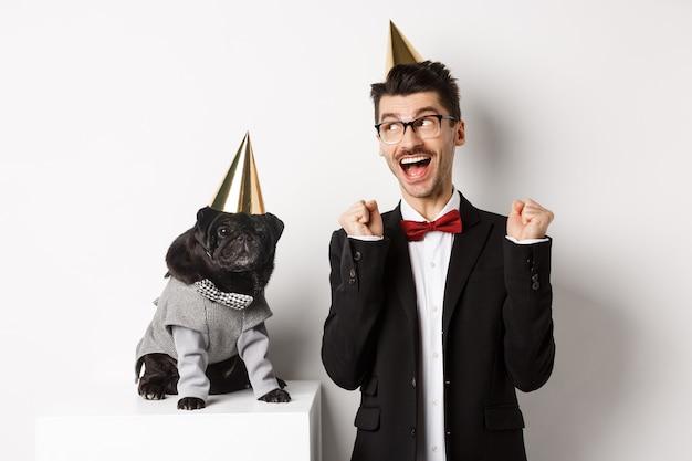 Giovane allegro che grida di gioia, cane e proprietario che indossano coni di festa di compleanno e festeggiano, ragazzo che si rallegra e fissa la macchina fotografica, sfondo bianco