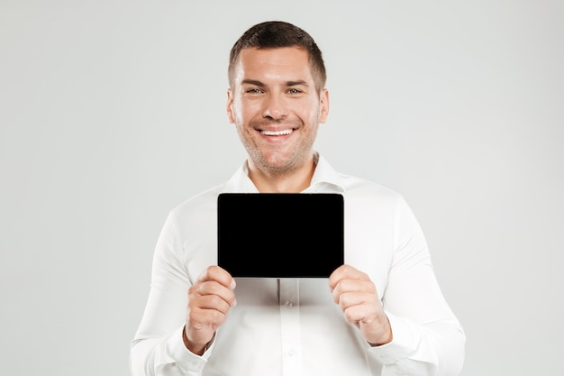 Cheerful young man showing display of tablet computer.