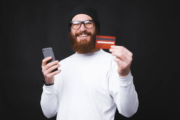 Cheerful young man showing his new credit card and holding smartphone