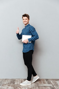 Cheerful young man showing thumbs up.