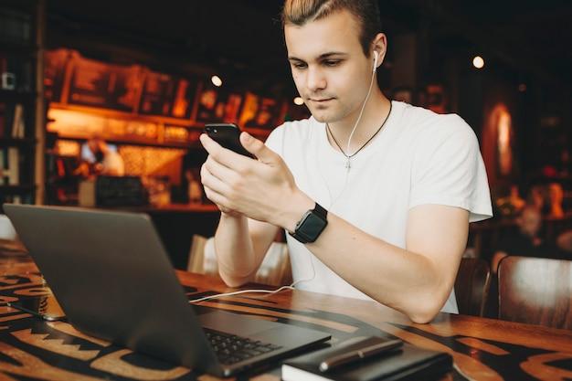 Веселый молодой человек сидит и просматривает смартфон за ноутбуком в кафе