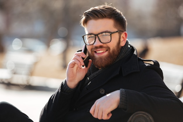 Веселый молодой человек сидит и принимает на мобильный телефон на открытом воздухе