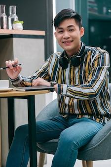 Веселый молодой человек сидит за столом в кафе с ноутбуком и улыбается