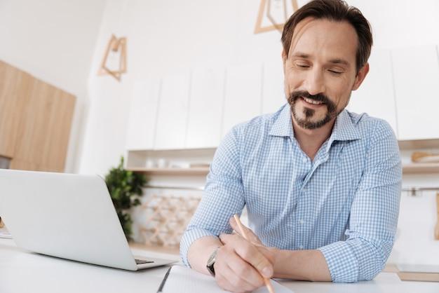Веселый молодой человек сидит за кухонной стойкой, держит карандаш и делает заметки, улыбаясь и довольный
