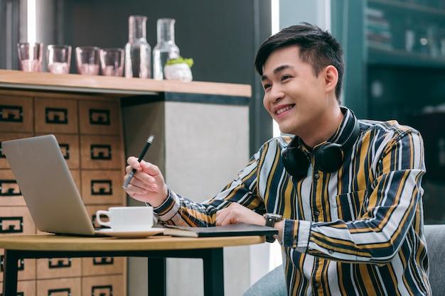 Веселый молодой человек сидит за столом с ноутбуком и чашкой кофе и с улыбкой смотрит в сторону