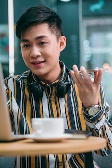 Веселый молодой человек улыбается и держит телефон при отправке голосовых сообщений