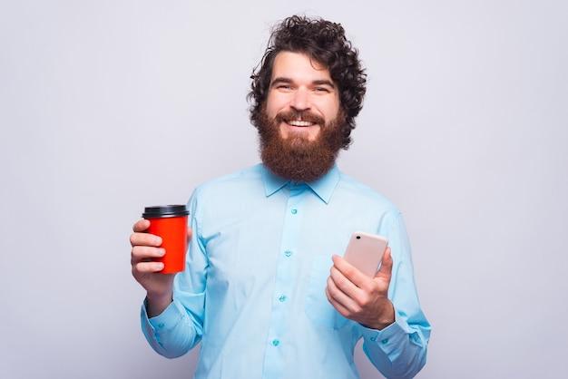 笑顔でカメラを見ている陽気な若い男は、温かい飲み物と電話でカップを持っています