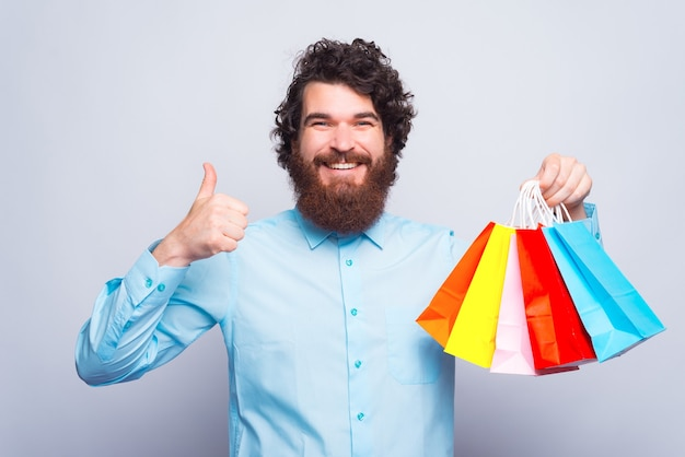 カメラに微笑んで、いくつかの買い物袋と親指を持ち上げて陽気な若い男