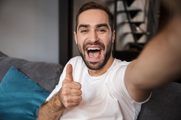 Cheerful young man taking a selfie while sitting on a couch at home