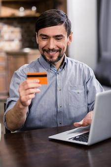 Веселый молодой человек, используя свою кредитную карту, сидя за столом