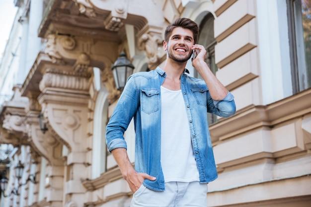 Веселый молодой человек гуляет и разговаривает по мобильному телефону в городе