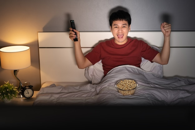 Cheerful young man watching sport tv with arm raised on a bed at night