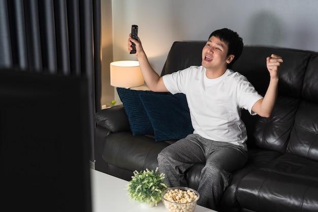 Веселый молодой человек смотрит спортивный телевизор с поднятой рукой на диване ночью