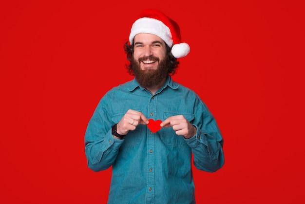 クリスマスの帽子をかぶって陽気な若い男は小さな赤いハートを持っています