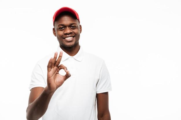 Cheerful young man wearing cap make okay gesture