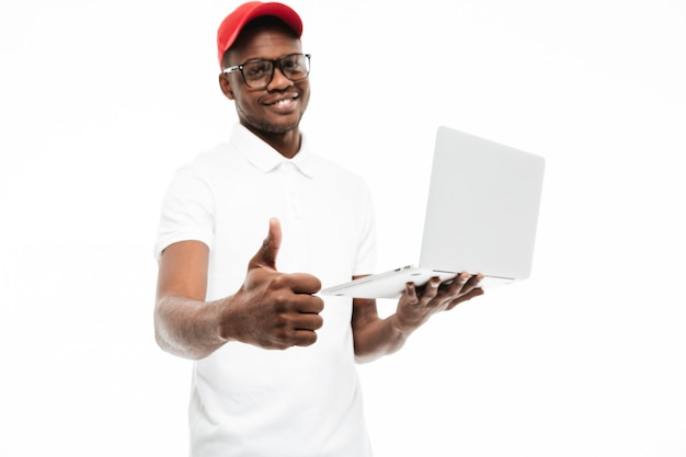 Cheerful young man wearing cap make thumbs up gesture