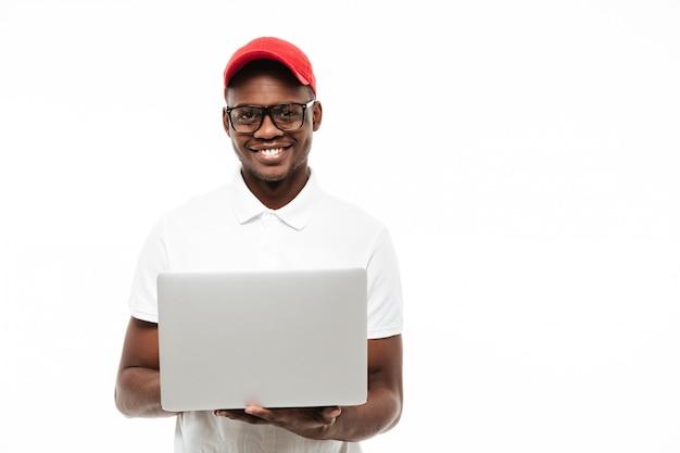 Protezione da portare allegra del giovane facendo uso del computer portatile