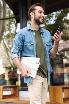 Веселый молодой человек в наушниках использует смартфон во время прогулки по городской улице с газетой и ноутбуком в руке