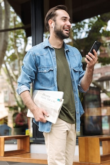 Cheerful young man wearing earpods using smartphone while walking through city street with newspaper and laptop in hand