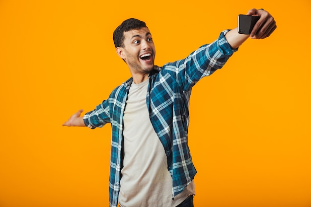 Cheerful young man wearing plaid shirt standing isolated over orange background, taking a selfie