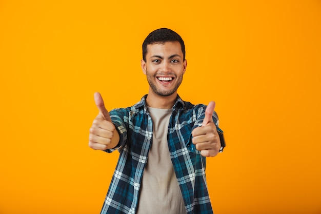 Cheerful young man wearing plaid shirt standing isolated over orange wall, giving thumbs up