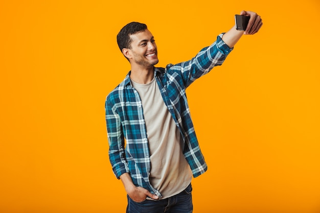 Cheerful young man wearing plaid shirt standing isolated over orange wall, taking a selfie