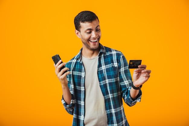 陽気な若い男が立っている格子縞のシャツを着てオレンジ色の背景に分離された、携帯電話を保持している、プラスチックのクレジットカードを表示
