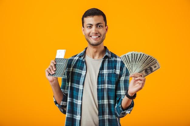 陽気な若い男がオレンジ色の背景に分離された格子縞のシャツを着て、紙幣を保持している、航空券でパスポートを表示