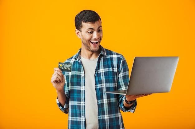 オレンジ色の背景の上に孤立した格子縞のシャツを着て、ラップトップコンピューターを使用してプラスチックのクレジットカードを示す陽気な若い男