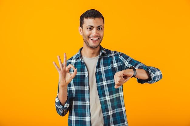 오렌지 벽 위에 고립 된 격자 무늬 셔츠를 입고 쾌활한 젊은 남자가 그의 손목 시계를보고