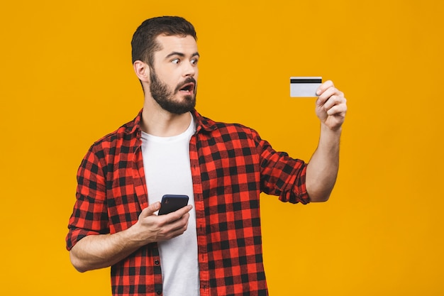 Cheerful young man wearing plaid shirt standing isolated over yellow wall, holding mobile phone, showing plastic credit card.