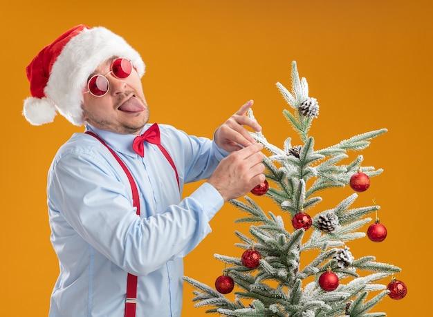 산타 모자와 빨간 안경에 멜빵을 입고 쾌활한 젊은 남자가 행복하고 놀란 나무에 장난감을 걸려 크리스마스 트리 근처에 서 오렌지 배경 위에 혀를 튀어 나와