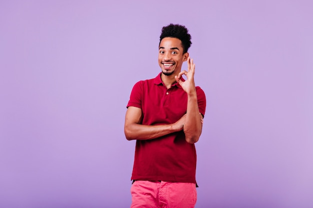 쾌활 한 젊은 남자는 괜찮아 기호로 포즈를 취하는 빨간 티셔츠를 입는다. 재미있는 아프리카 남성 모델입니다.