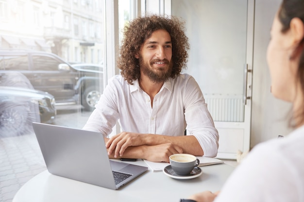 Cheerful young man with beard and brown curly hair meeting friend in coffee shop, working remotely with modern laptop, sitting at table near window with folded arms