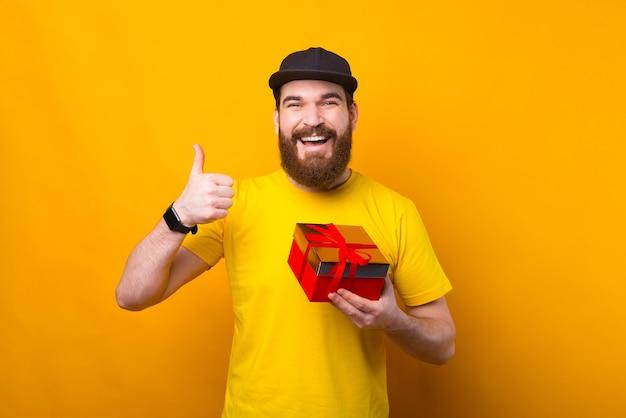 선물 상자를 들고 노란색에 엄지 손가락을 보여주는 수염을 가진 쾌활 한 젊은 남자