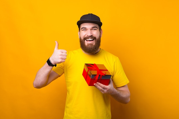 Cheerful young man with beard holding gift box and showing thumb up on yellow