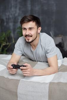 수염을 가진 쾌활한 젊은 남자가 침대에 누워 자기 격리 중에 게임 콘솔에서 놀고
