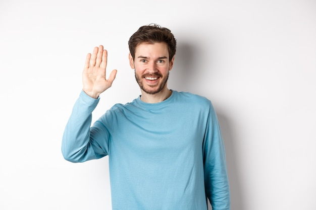 Cheerful young man with beard saying hello, looking friendly and waving hand to greet you, standing over white background.