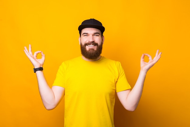 Cheerful young man with beard on yellow making zen gesture and smiling, peaceful and relaxing time