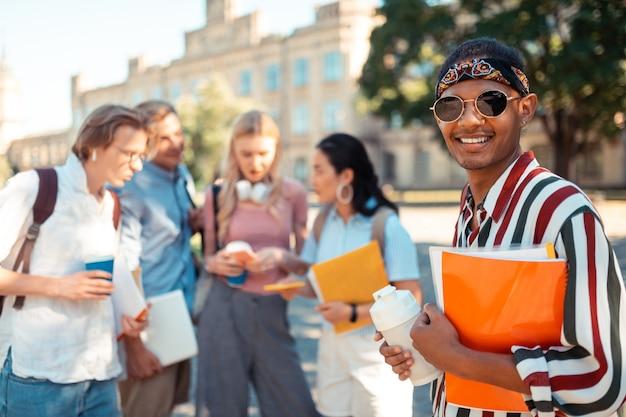 Веселый молодой человек с книгами и бутылкой воды в руках стоит во дворе университета