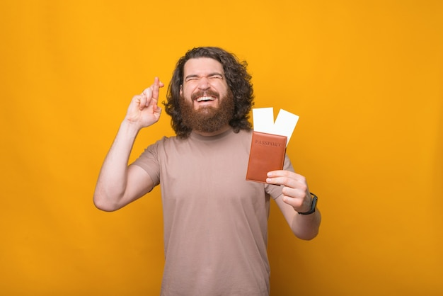 Веселый молодой человек с вьющимися волосами, держащий паспорт с билетами и скрещивающий пальцы, хочет путешествовать